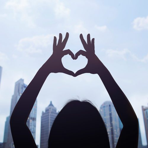 Woman in Shanghai's Pudong District making a heart symbol with her hands